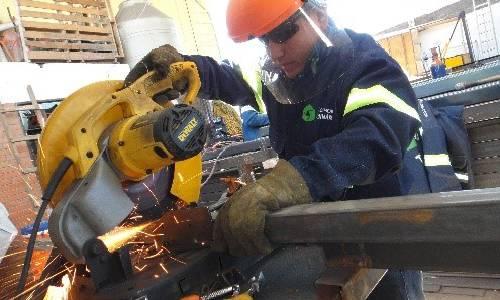 trabajador cortando estructura metalica